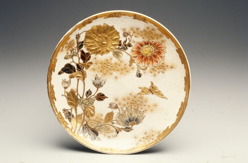 Gold rim with raised designs; spray of large flowers with raised gold outlines and green, brown, and red highlights; butterfly at left; gold dots throughout background