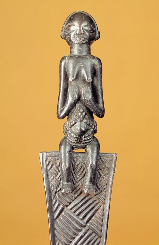 Female figure seated on top of a fan-shaped element decorated with basketweave carvings; small flared area with carved ribs at bottom