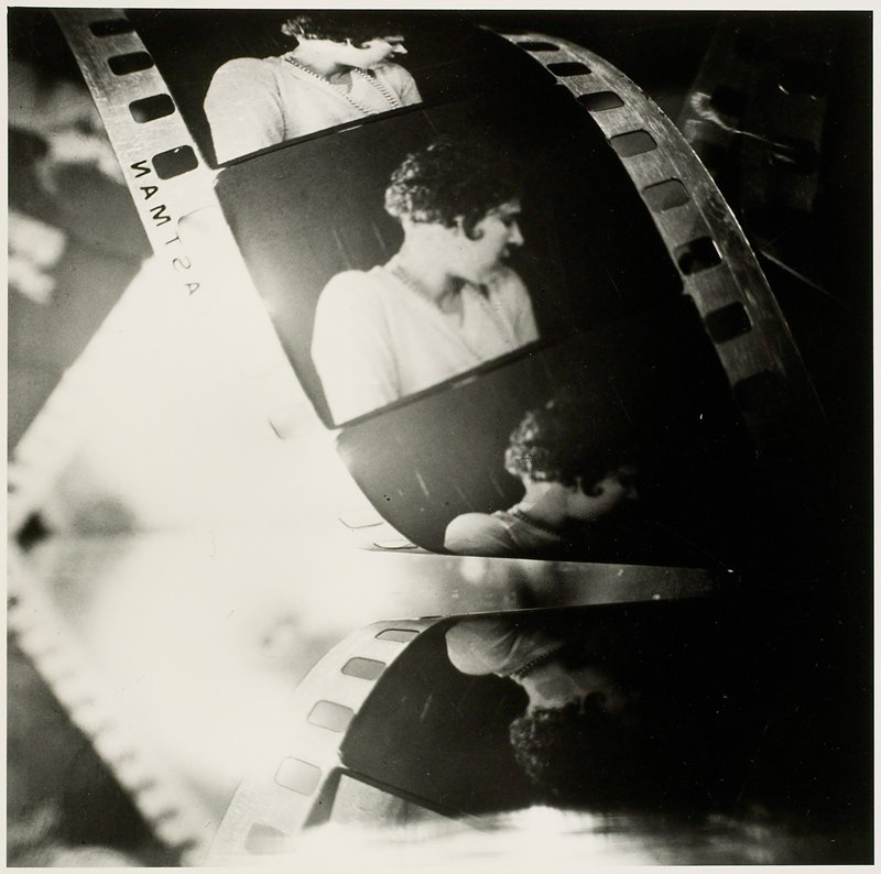 curled strip of film; fair visible images of a woman with ear-length dark hair on strip