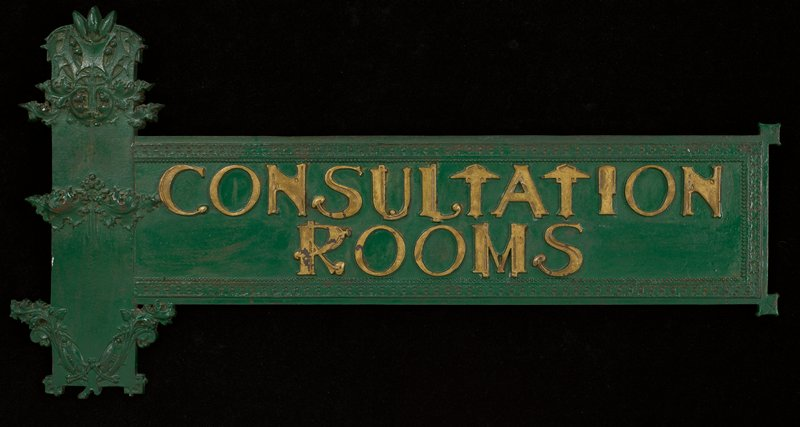 green with gold letters; rectangular with vertical rectangular element with leaves and organic designs in relief at left