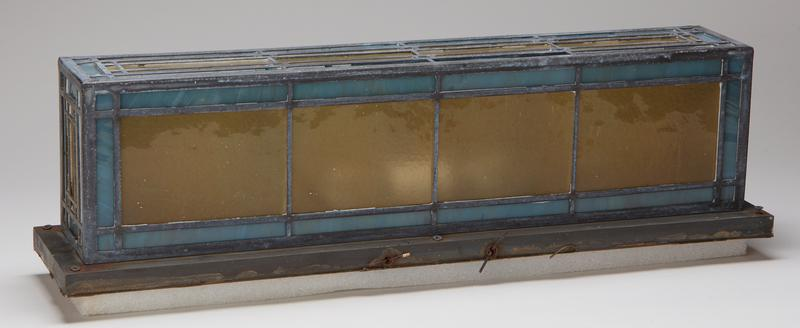 rectangular shape; block designs on 4 sides of light blue, dark blue, purple, yellow, red and green leaded glass; wall-mount design