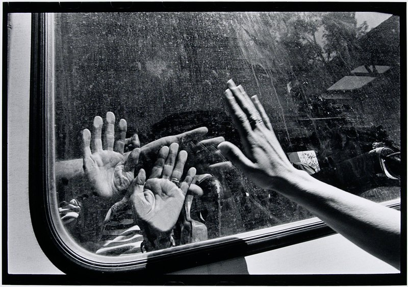 hands on window, another waving