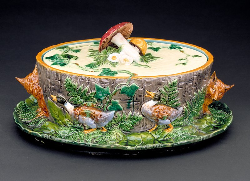 lead-glazed earthenware called 'Majolica' in shape of oblong dish with leaf form flange at bottom, raise figures of foxes and ducks along sides; lid handle in the forn of a bunch of mushrooms, leaf and vine pattern on lid top; interior is turquoise, exterior is multicolor