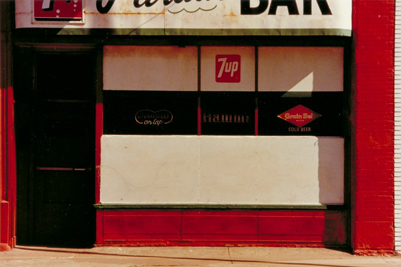 front of bar; 7-Up and Grainbelt signs, red brick