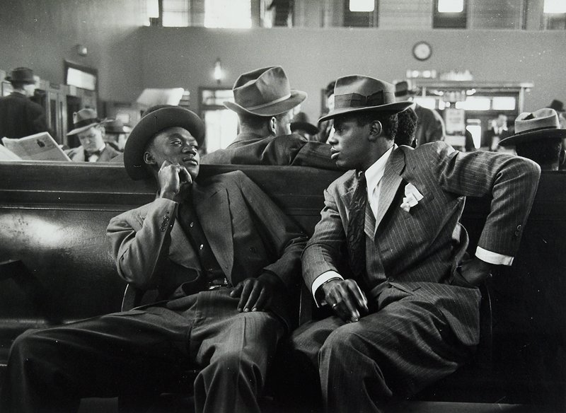2 black men wearing suits and hats seated on a bench, turning to face each other; other men wearing hats seated in background; matted