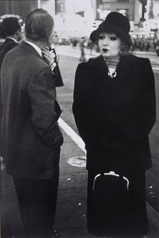 woman wearing dark suit and gloves, veiled hat and heavy makeup carrying a handbag with a metal clasp; 2 men at L seen from back