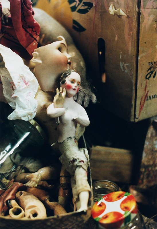 Small broken doll head and torso resting on another doll's cloth body; large broken doll head behind; box with doll limbs at LL corner; soiled tissue, bits of cloth, jars and cardboard box scattered throughout
