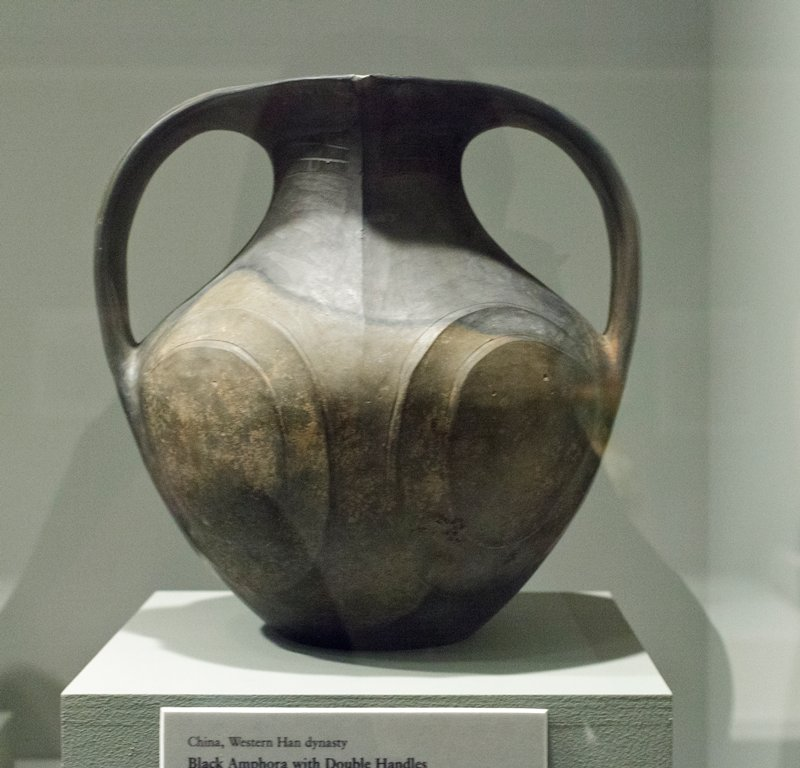 black ovoid amphora with 4 oval-shaped incised designs on body; 2 bowed strap handles; mouth has 2 points