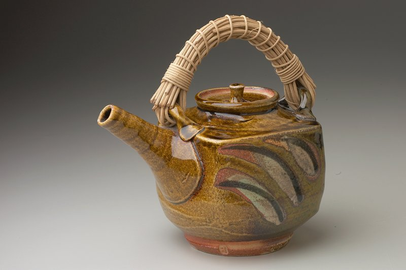 teapot with squared corners; thrown spout; plant fiber handle at top; brown glaze with dark brown, green and wax resist leaflike decorations on 3 sides