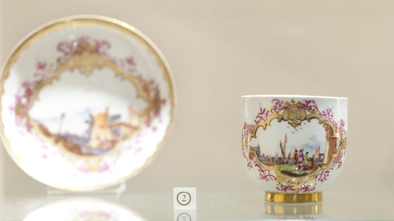 Teacup and Saucer, ceramic, cat. card dims diam 2-3/4 x H 2-3/4' White ground with scenes of ships landing in panel on cup and landscape panel with bridge on saucer with border of gold and lavendar.