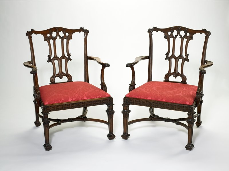 pair of armchairs, carved mahogany with upholstered seats; numbered IV and VIII in wood under seat; George II period