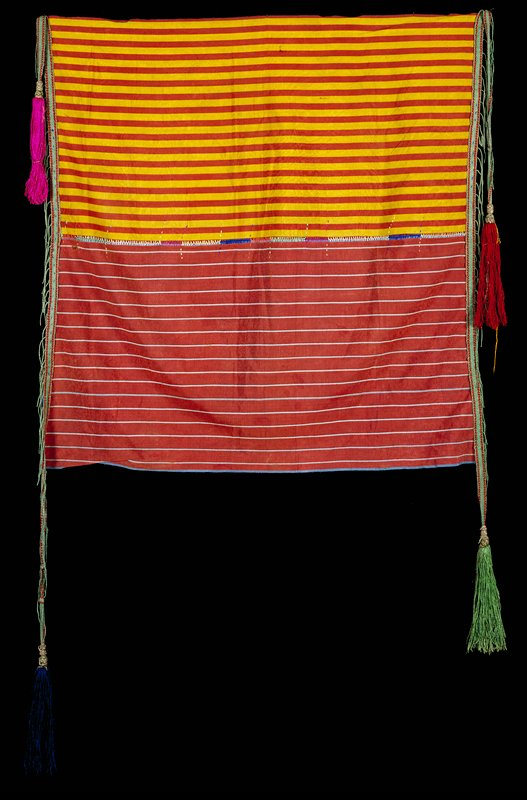 2 panels seamed with embroidery stitch; ground is striped gold, rust, and rust and white, green, blue, dark red, pink, white; 4 tassels; 2 green braided bands