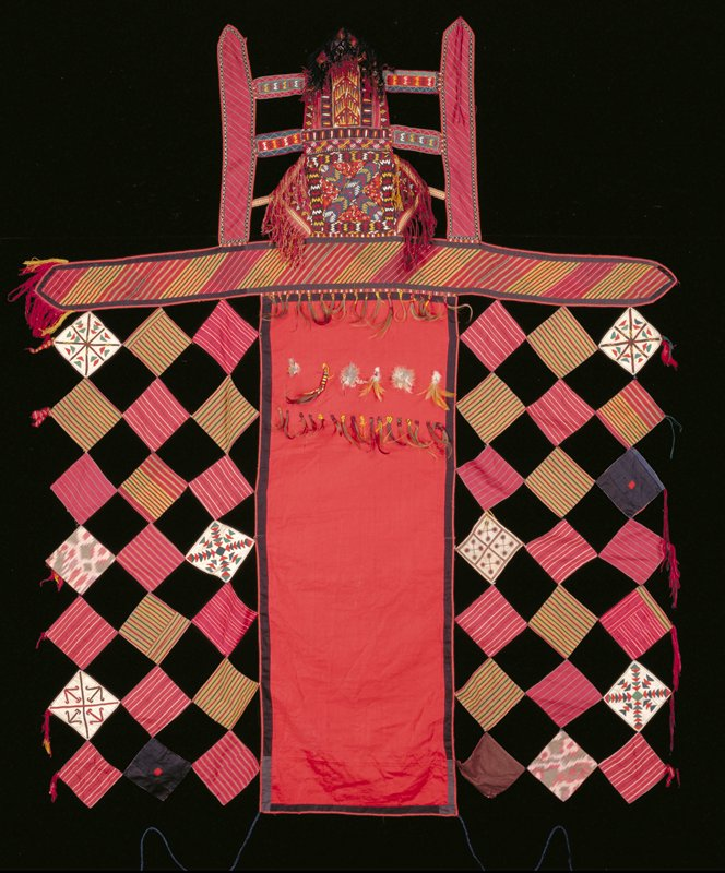 large central red panel, flanked with fabric squares, some embroidered, some plain, striped and ikat; tufts of hair and feathers; top portion consists of vertical and horizontal bands stitched together embroidered with fringe