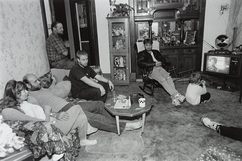 black and white photo of four men, a woman and child seated in living room with television