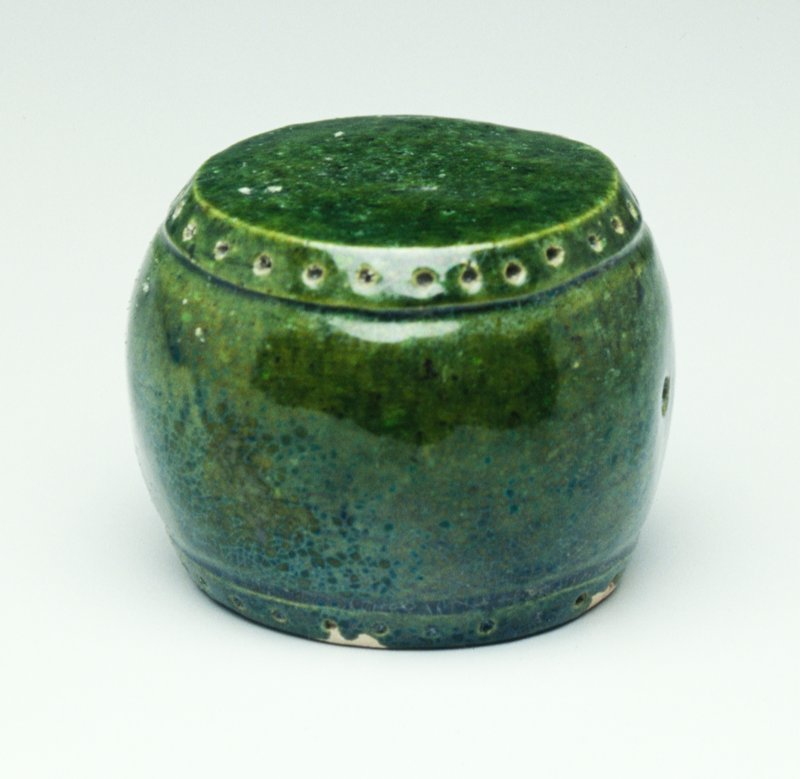 Tomb furniture; small stool, flat on top and bottom with slightly flaring middle section; decorated with row of incised dots around top and bottom edges with incised line; 2 holes in sides opposite each other; glazed green