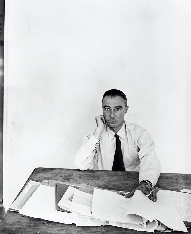 man wearing white shirt and tie; PR hand on check; PL hand holding cigarette and papers on table; white wall behind man