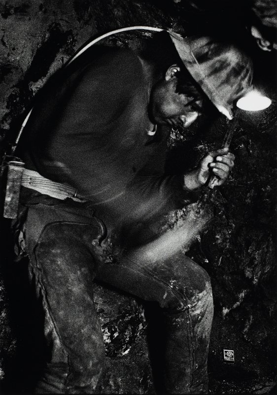 miner with lit helmet; he's on his back with tool in his hand