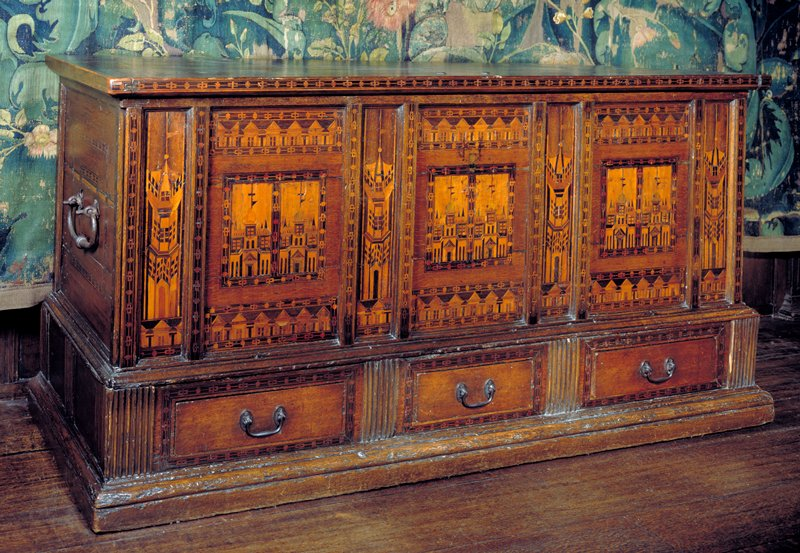 three panels of façade inlaid with designs of Nonesuch Palace, upper and lower portions with dormer windows of the same; panels framed by bead-and-real border; three drawers in lower portion; hardware of iron