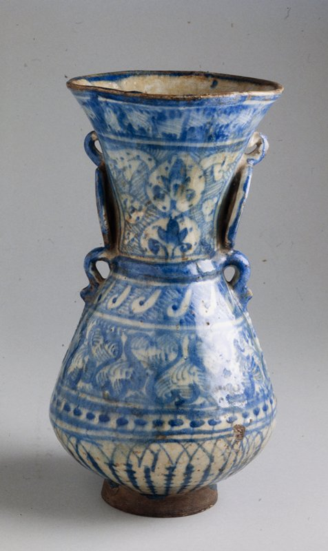 Footed vase with applied ring handles, earthenware with chinoiserie motifs in underglaze cobalt blue. H. 13-3/4 in. Signed Amal Abu'l-Ezz. Imitates vases of Yuan Dynasty (1280-1368), Chinese celadon although also influenced by shape of mosque lamps of the Mamluk period.
