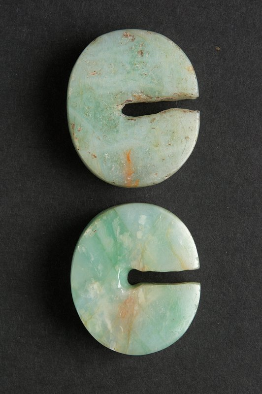 2 oval-shaped discs with flat sides; slightly wider at bottom; light green with red/orange areas/streaks