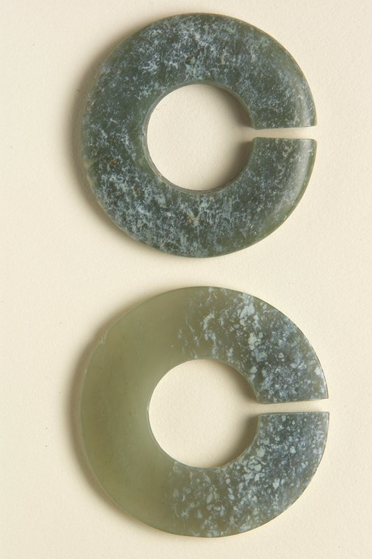 pair of round earrings with open centers; green and white mottled jade; a mottled on top half, semitransparent light green on bottom half