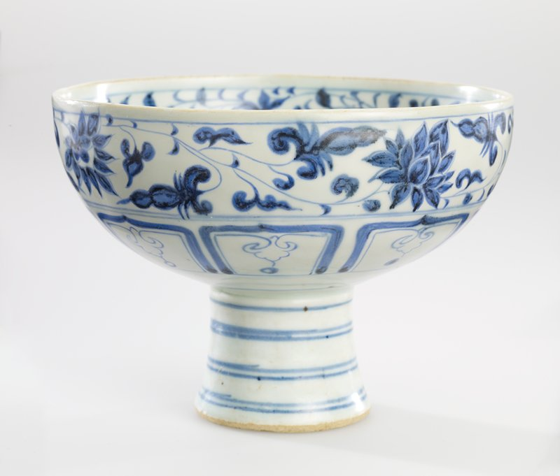 blue and white glaze; bowl on a tall, slightly flaring stem; foliate spray at center; foliate bands on interior and exterior rim with geometric design band below on exterior; blue rings on stem