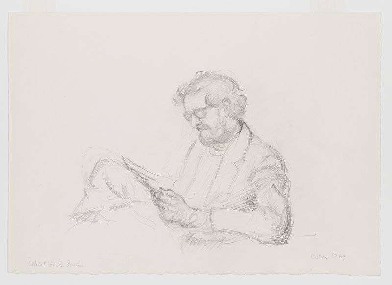 portrait of seated man, in profile from PL, looking at a piece of paper held in his PL hand; man has shaggy hair, beard and wears glasses and a jacket