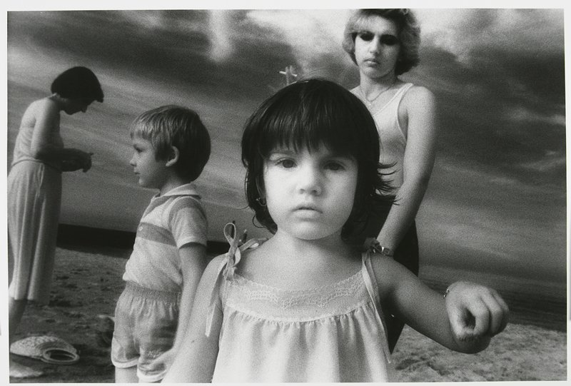 little girl with dark hair in foreground, head and chest visible, facing camera, with her PL arm raised, holding a small object; blonde woman smoking a cigarette behind her; little boy wearing shorts at L; woman in a dress at far L; on a beach