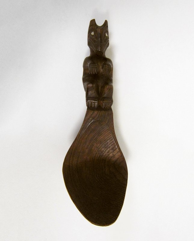 Large wooden ladle carved in shape of horn spoon with sea-monster on handle. he has the killer-whale's head with long face and teeth and the bears' body. The eyes are set with mother-of-pearl. He is represented as sitting carefully balanced on small projection from the bowl of the spoon.