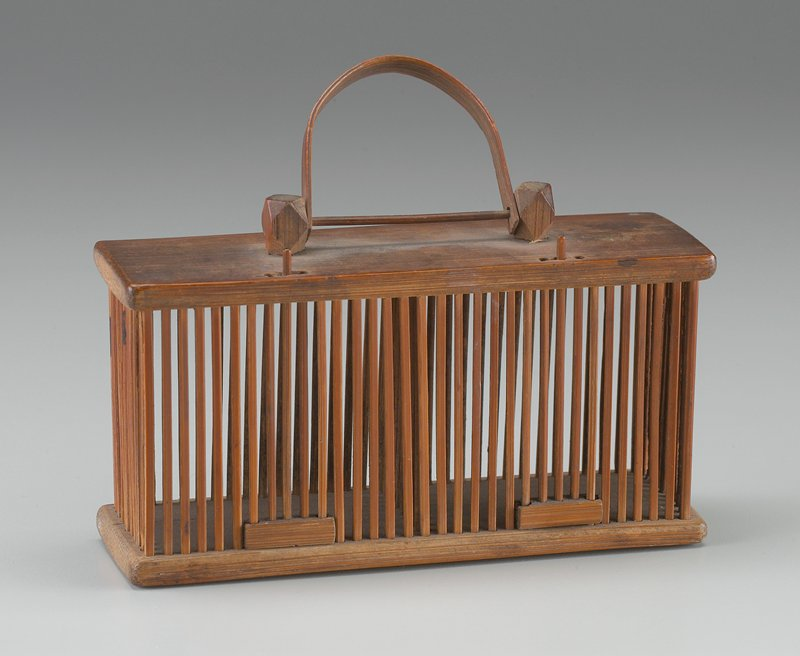 rectangular cage with slats at center dividing it into 2 parts; 2 sliding doors; small bamboo handle on top