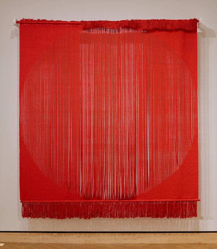 red linen; solid background with a circle defined by vertical stripes 1/2 in. wide warp face; at the top left the warp is braided (1 x 28 in.); one metal rod (covered with the warp) at the top, one at the bottom; fringe 8 in. at the bottom; fringe 5-1/2 in. decrease to 2-1/2 in. at the top