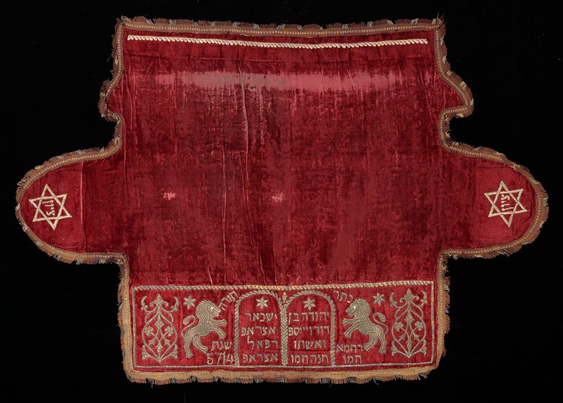 thick red velvet with brown and metallic trim; metallic embroidery on front of 2 floral scrolls and 2 rearing lions flanking a pair of tablets with text; stars with text embroidered on each side; green silk backing