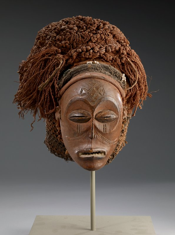 Mask, Chokwe, Mwana Pwo, about 1910. Wood, braided and netted raffia headdress, white beads. mask, H.7-1/4 in. Headdress H.10-1/2 x W.10-1/2 in. Masoji-scarification marks in form of tears below each eye. Tshingelyengelye-cruciform mark with circular terminations in center of forehead. Portion of earlobes missing just below where ears were pierced.