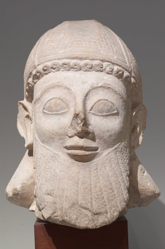 Helmeted and bearded head of a votary of carved limestone; in the archaic Cypriote style; the beard radiating with intersections; the helmet is quilted and framed and allows one row of curls to show above forehead. Ears are showing; a vigorous representation in nearly perfect state of preservation. From the temple of Golgoi. ;votary in the temple of Golgai; head only; archaic, cypriote style; radiating beard, quilted helmet; archaic smile; strong frontality
