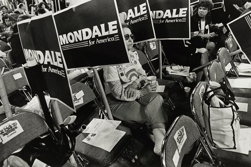two women seated on folding chairs with four 'Mondale for America' signs