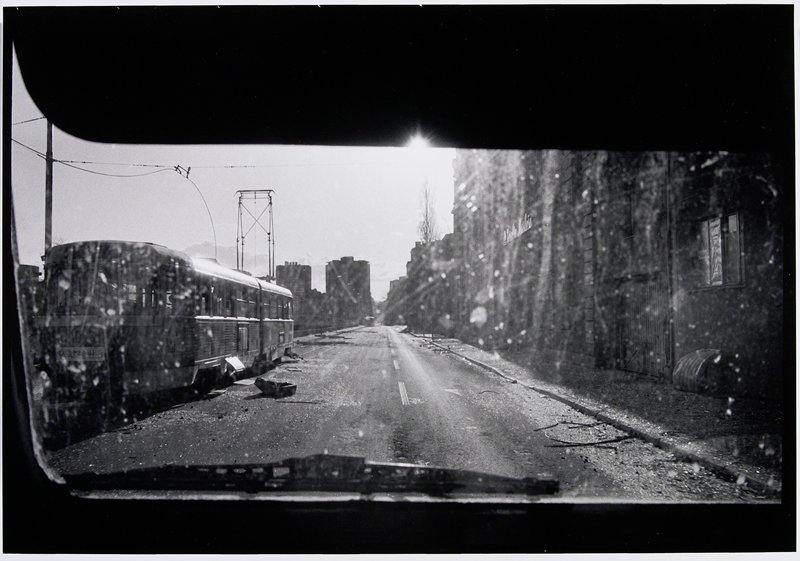 trolley and abandoned road in sunlight through dirty automobile window