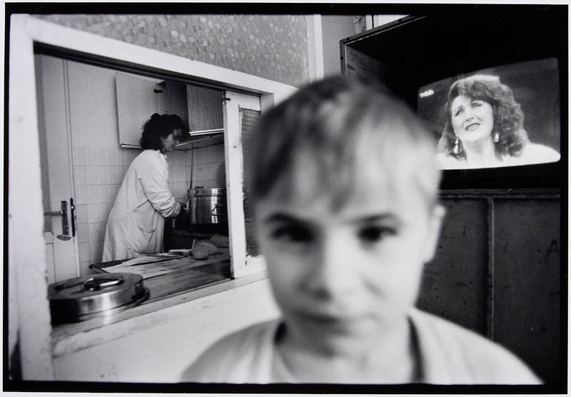 blurry boy's face, woman in kitchen and television on