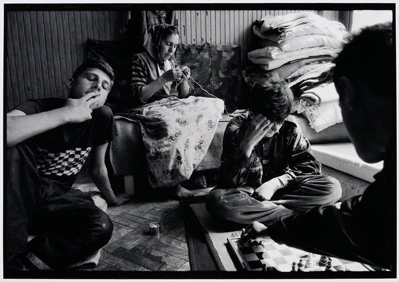 people playing chess, knitting and smoking