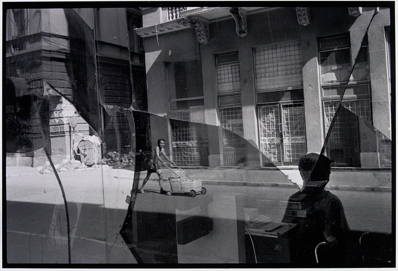 looking through broken window to a man pushing cart with three boxes