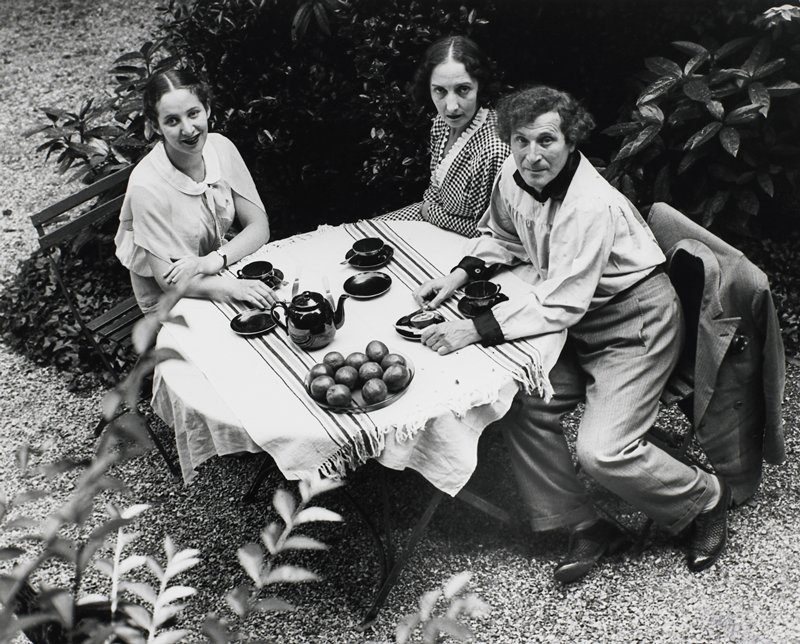 three people seated at a circular table, two women and one man; shot from above