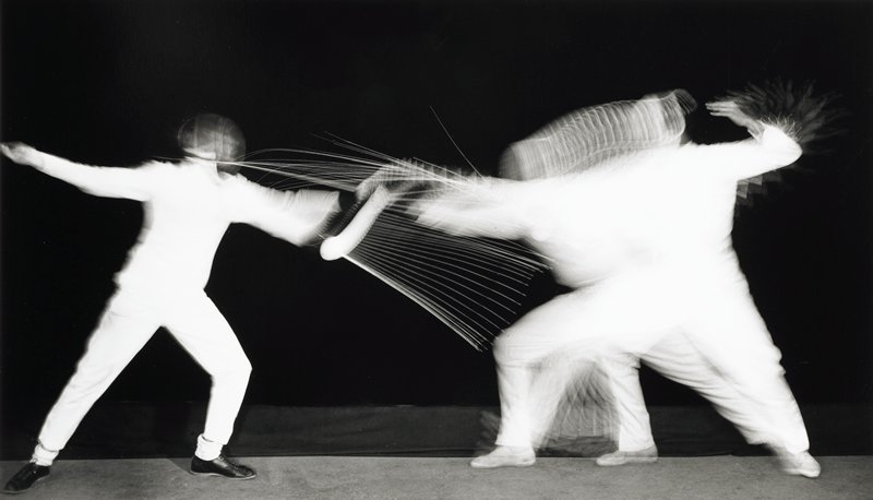 multiple exposure image of two figures in white, fencing