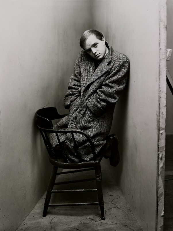 man wearing a coat, kneeling on a chair in a corner