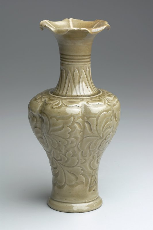 Celadon vase, from the yaozhou kilns; porcelain; baluster body divided into 6 lobes and vigorously carved with an overall pattern of peony scroll, trumpet neck lobed to match and flaring mouth with frilled rim; glaze of characteristic olive green tone; grayish stoneware body revealed at unglazed rim of foot.