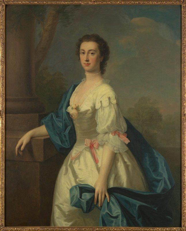 Three quarter length portrait of a lady in white dress with a blue satin scarf draped over right arm and shoulder, and wrapped around the figure to be held in left hand. Pink ribbon knots at belt and sleeves and pink rose at breast. The girl has dark hair and wears a necklace of pearls. She is leaning with her right arm on a column and there is a landscape in the background. Wide scrolled gold frame.