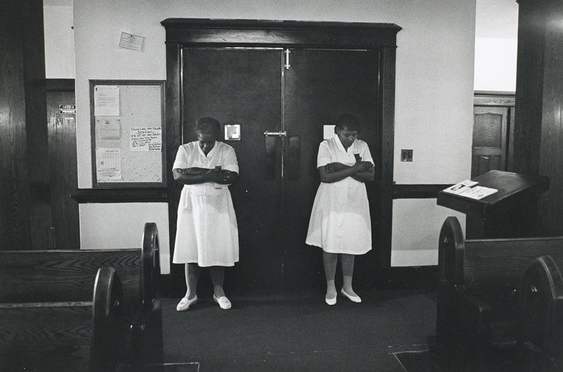 black and white photo of two women in white, heads down