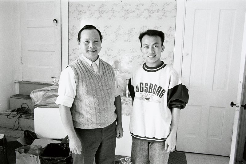 black and white photo of two men standing in room; man on right is wearing 'Augsburg College' sweatshirt