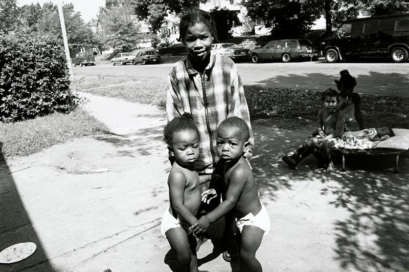 black and white photo of girl in plaid shirt standing behind two children in diapers