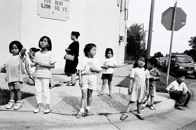 black and white photo of two women and seven children on corner; 'For Rent' sign behind them