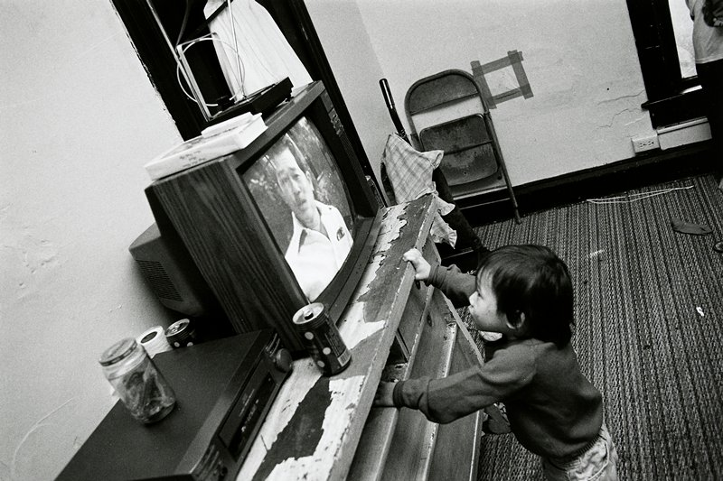 black and white photo of child reaching up toward television