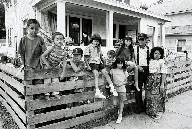 black and white photo of man and woman, seven children in front of house